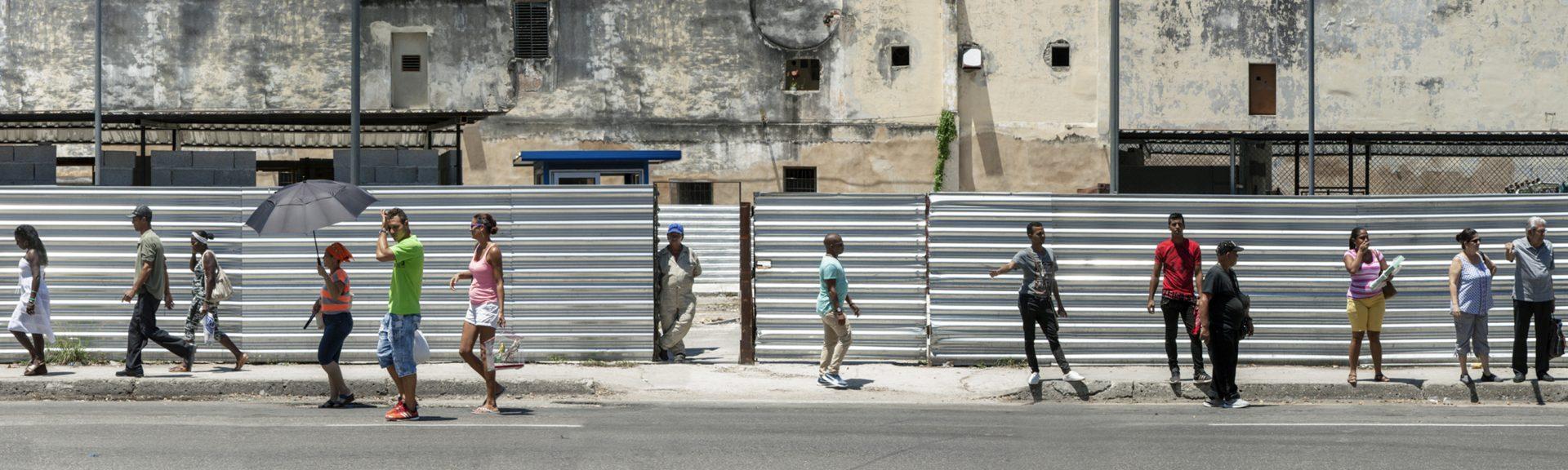 passants devant une palissade à la havana, cuba.
